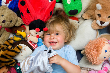 little child in the middle of plush toys