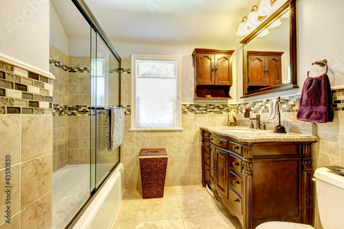 Nice bathroom with natural stone tiles and wood cabinet.