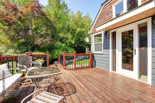 House exterior with large open deck with outdoor furniture.