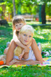 Young blonde plays with her ​​daughter in the park