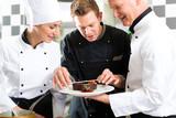 Team von Köchen mit Dessert in Küche