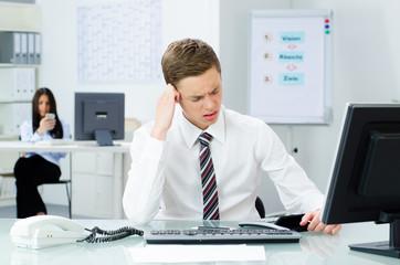 geschäftsmann sitzt gestresst vor seiner arbeit