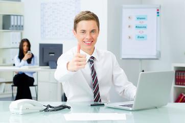 erfolgreicher jungunternehmer zeigt daumen hoch