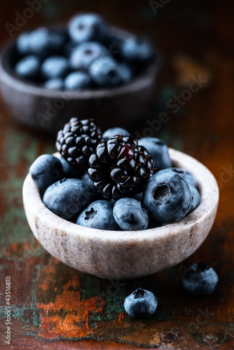 Blueberries and blackberries in small dishes