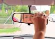 Frau richtet den Rückspiegel im Auto