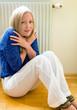 Frau sitzt vor einem Heizkörper