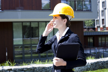 Young female construction engineer with phone