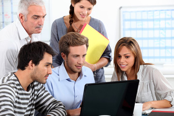 Informal team of people sitting round a laptop computer