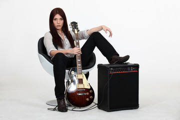 Female guitarist sitting with an amp