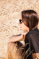 Junge Frau sitzend am Sandstrand
