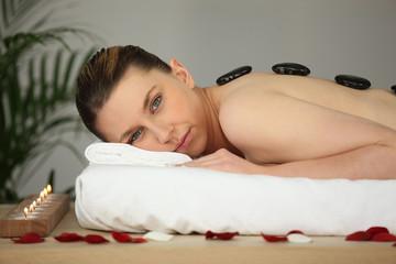 Woman receiving a hot stone treatment
