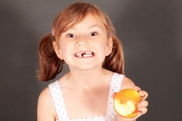 Kind mit Zahnlücke isst Apfel
