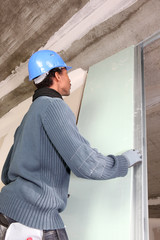 Man installing plaster board panel
