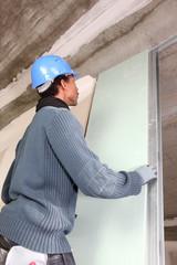 Man installing plaster board panel