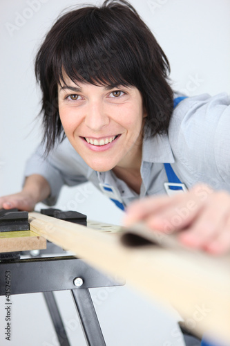 Woman sanding a plank of wood