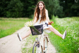 Fototapety Woman riding bicycle with her legs in the air