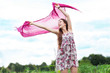 Young woman holding pink scarf to wind