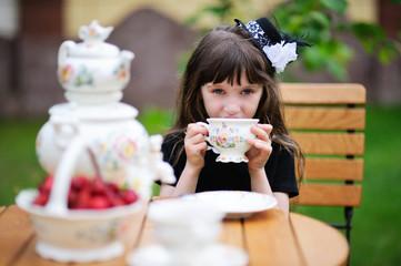 Elegant child girl having a tea party outdoors