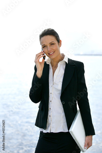 Smart businesswoman on cellphone outdoors