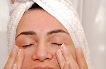 donna che applica crema sul viso