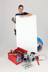 Woman with blank board, toolbox and cellphone
