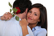 Woman holding single red rose and hugging husband