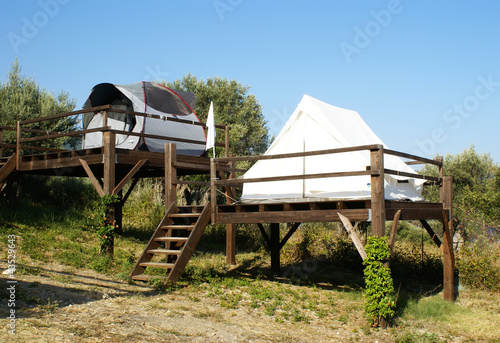 tents on stilts over the blue sky and countryside. Camping