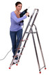 Woman on a stepladder with a powerdrill