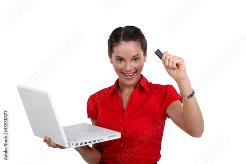 Happy woman with a USB key and laptop