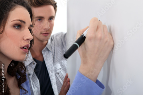 Couple working at a whiteboard