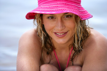 Blond woman wearing a pink hat at the beach