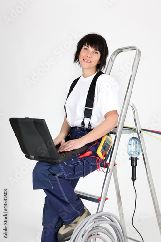 Female electrician sat on ladder with laptop