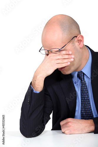 tired businessman rubbing his eyes