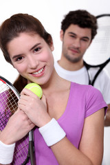 Young couple with tennis equipment