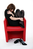 Woman curled up in a chair after a bad day