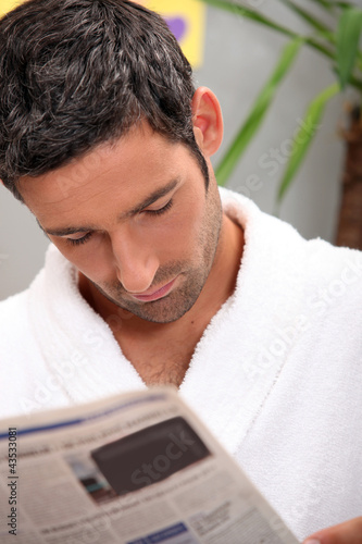 Man reading morning newspaper in kitchen