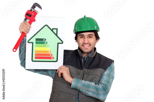 Tradesman holding a pipe wrench and an energy sign