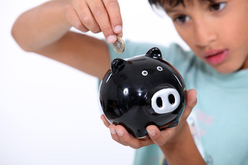 boy putting a coin into a money box