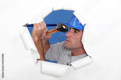 Manual worker using hammer and chisel