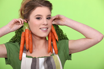 Funny woman holding carrots to her ears