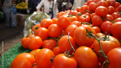 Tomatoes for sale in a busy market.