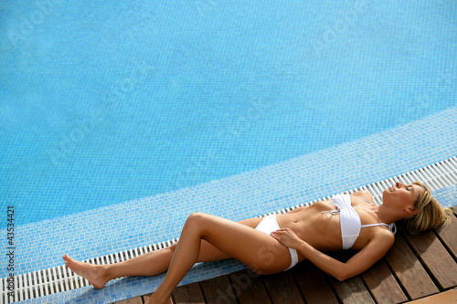Gorgeous woman laid at the poolside
