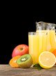 fresh tropical fruits and juice in glass isolated on black