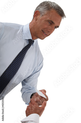 Senior businessman holding out business card