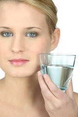 Blond woman with glass of water in hand