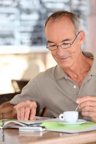 Old man drinking coffee and reading