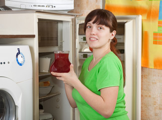 woman putting jug with fruit-drink into fridge