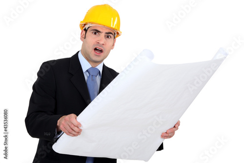 Outraged engineer examining a construction drawing