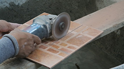 Craftsman cutting the tile by circular saw