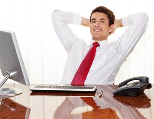 Erfolgreicher Manager sitzt bei Schreibtisch